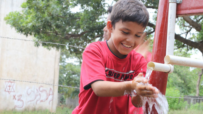 A young boy in splashing water from a well at Santa Rita community
