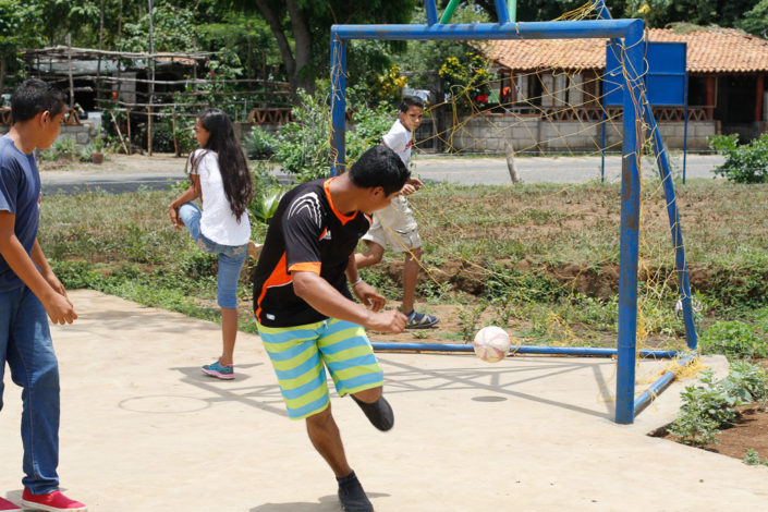 Teenage boy playing soccer at the Sequira community sport court
