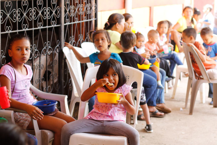 Young girl eating lunch at Los Cedros community feeding program